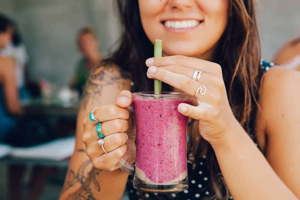 Happy woman drinking an Acai smoothie