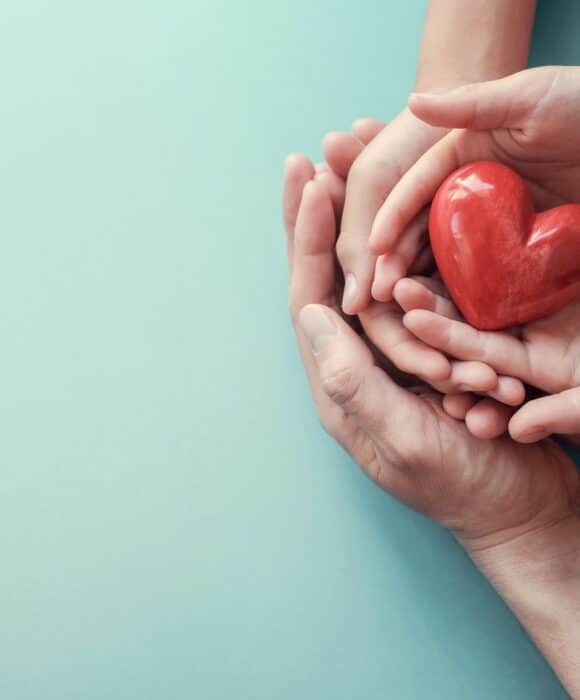 Hands holding a heart shaped apple for World Health Day