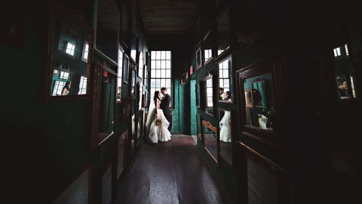 Bride and groom kiss in a mirrored hallway