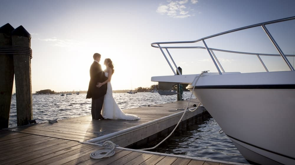 Bride and groom on a dock by the water