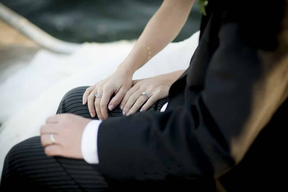 Bride and groom show off wedding rings