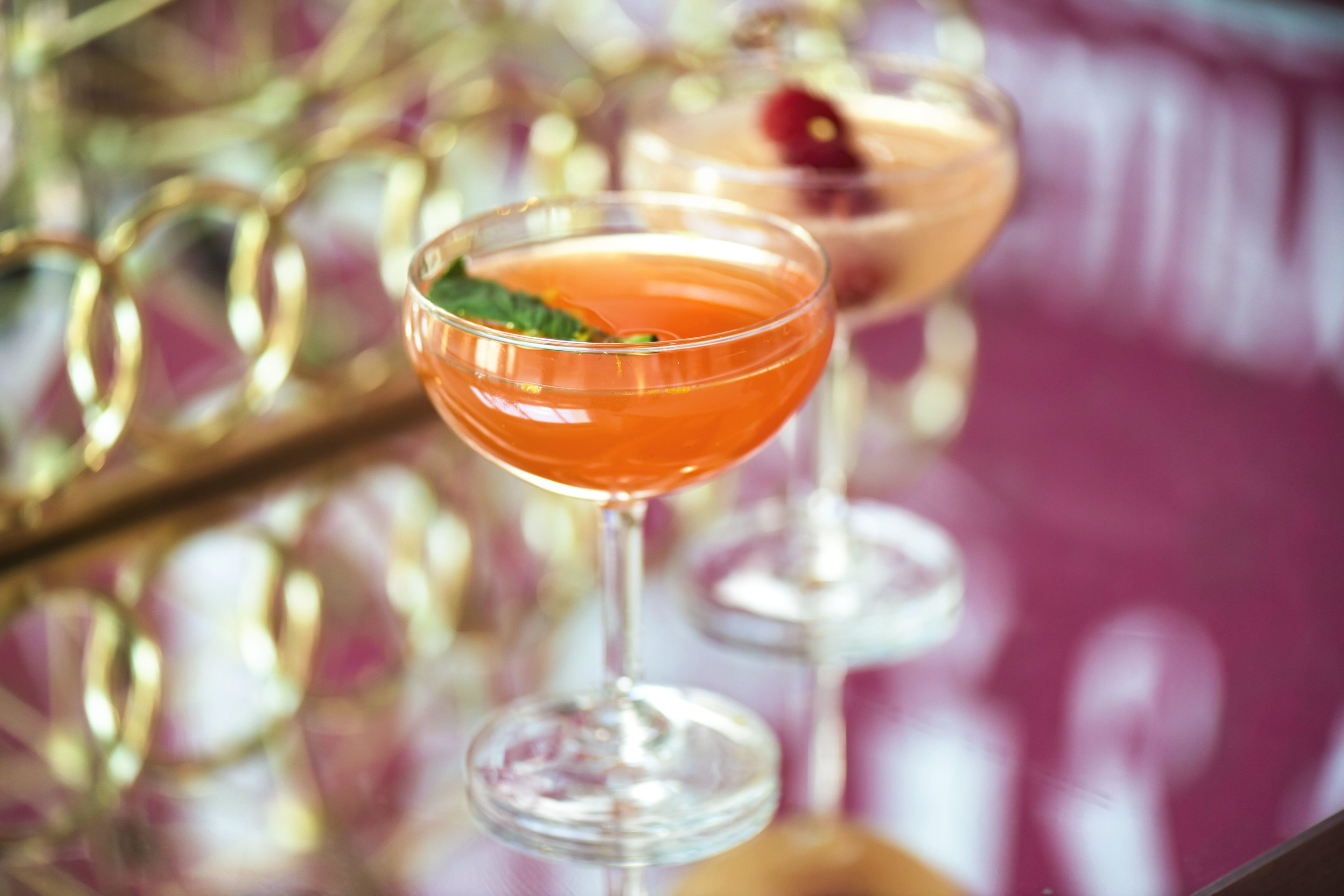 Orange and gold cocktails in coupe glasses