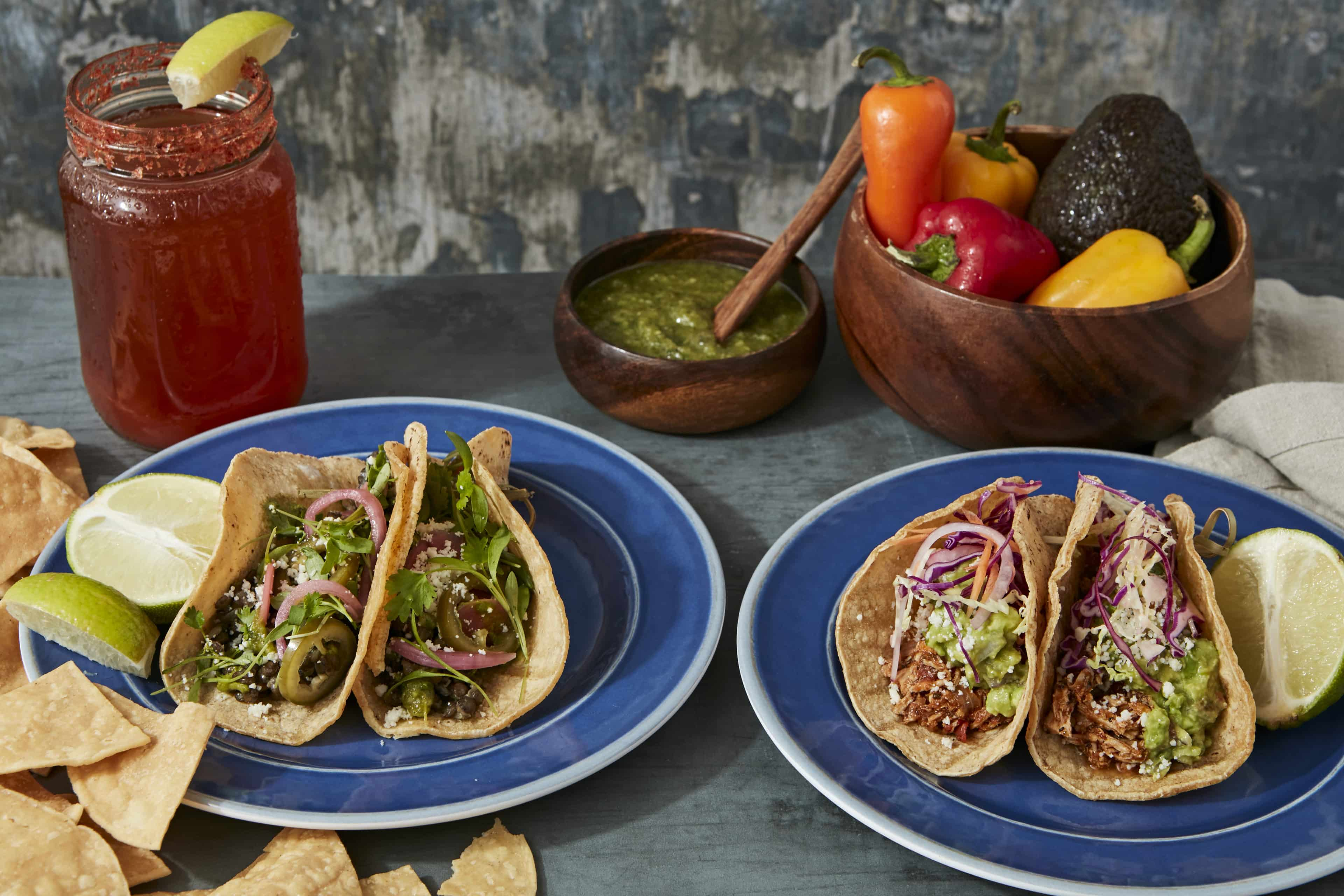Plated tacos, salsa verde and chips, michelada
