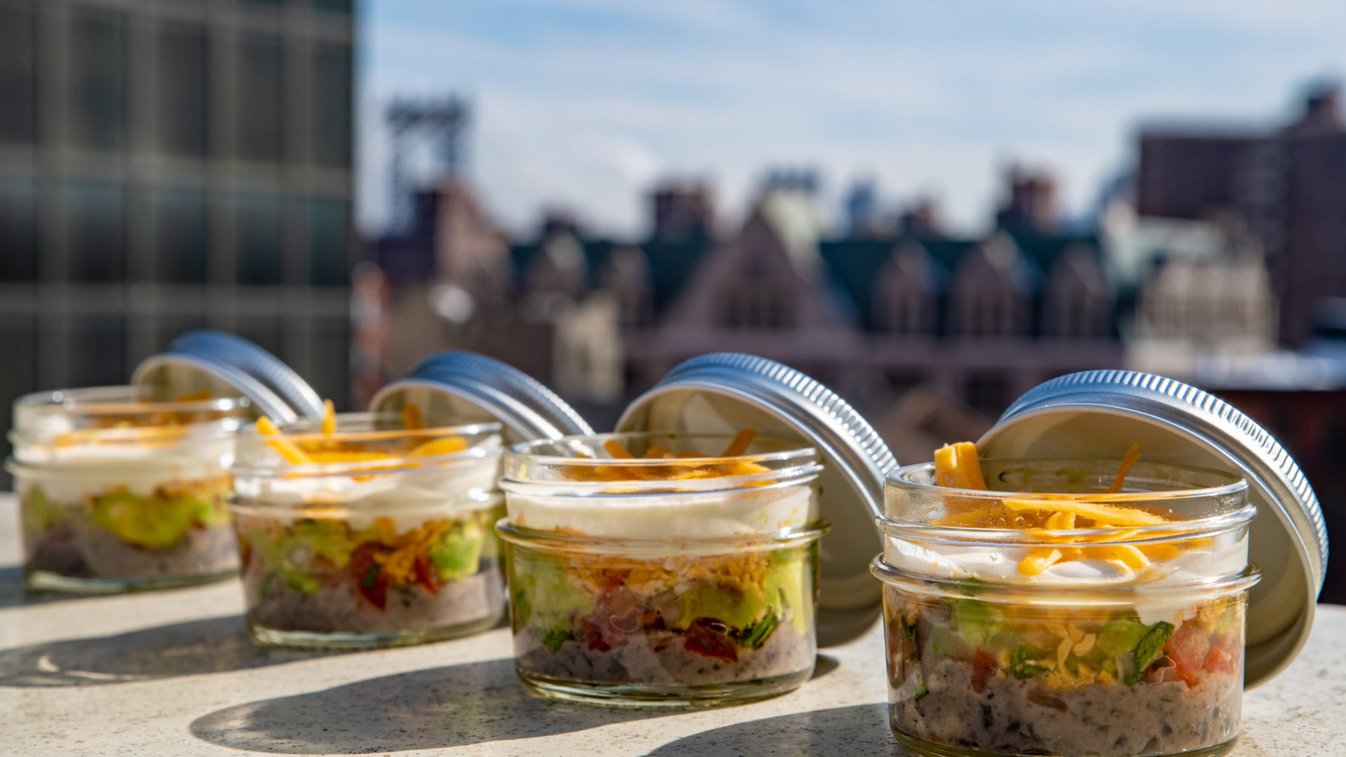 Five layer dip in mason jars, cheddar cheese