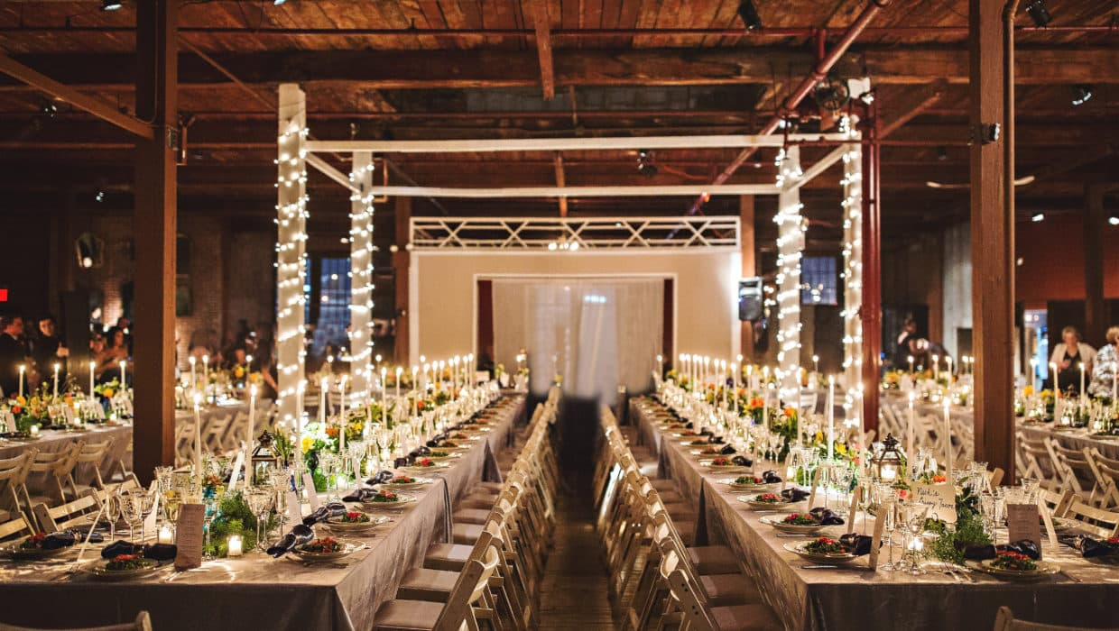 Full room shot with candles lite, long long tables