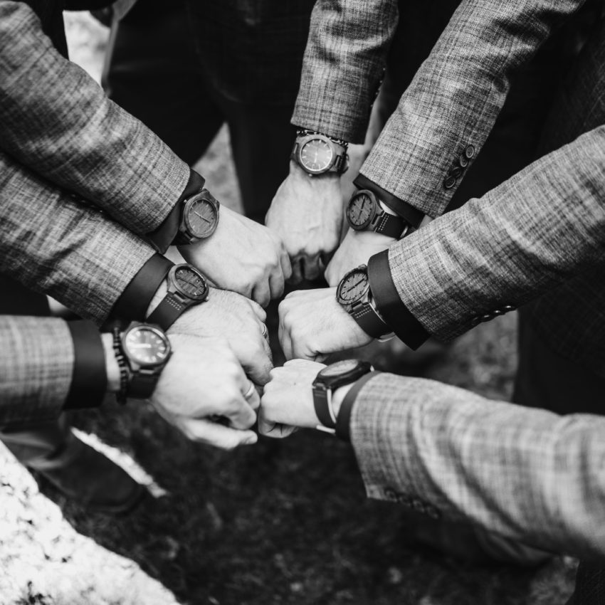 Groomsmen show off their matching watches in a circle