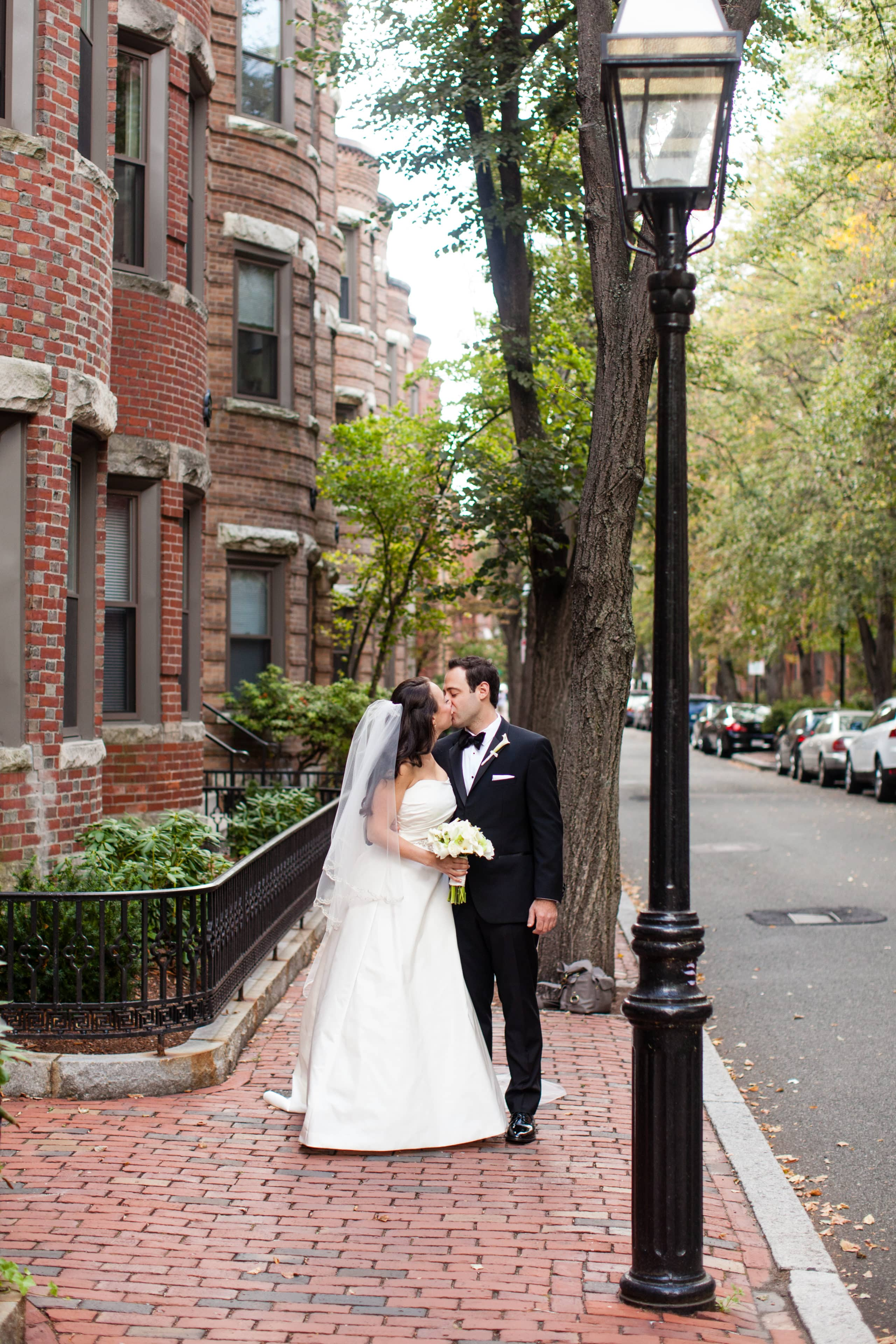 Just Married, this happy couple shares an intimate kiss on the sidewalk under a lamppost