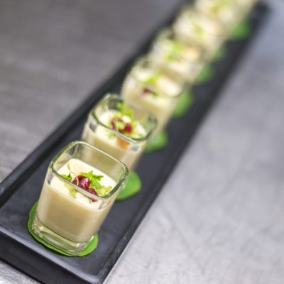 Passed Hors d'Oeuvre in individual glass shooters on a black tray