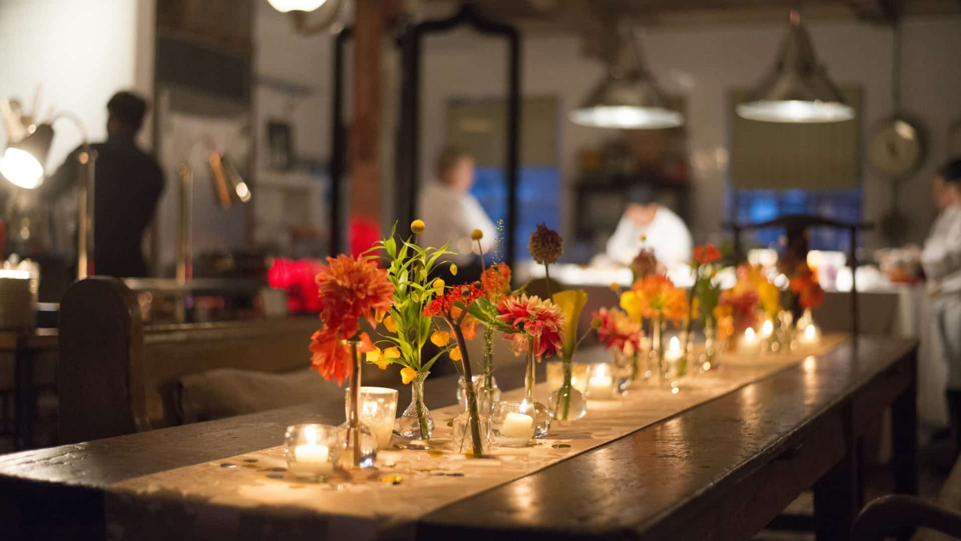 Florals and candles on a runner down a wooden kitchen table