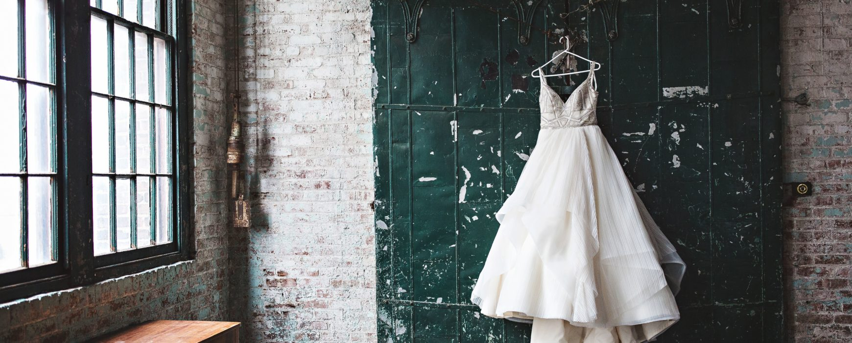 Wedding dress hanging on a sliding barn door